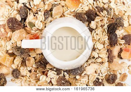 White Milk Pot With Plant Milk, On Pile Of Muesli With Dry Fruits, Closeup Background.