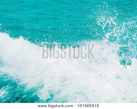 Splashing water in blue turquoise sea background