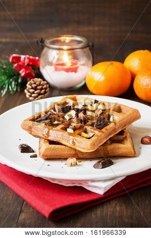 Homemade classic waffles for christmas breakfast on white plate on rustic background with clementine selective focus vertical