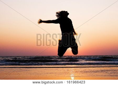Silhouette of a man jumping at the beach during sunset