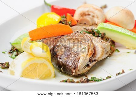 Roasted dorada fish with vegetables and mushrooms on white plate