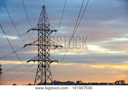 Electricity pylons and power lines silhouettes at a cloudy sunset over urban skyline