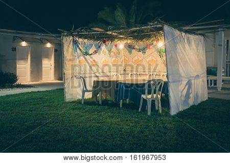 Fabric sukkah decorated with printed pattern and hebrew text of blessing: Grant peace everywhere goodness and blessing Grace lovingkindness and mercy to us and unto all Israel Your people. Night toned image