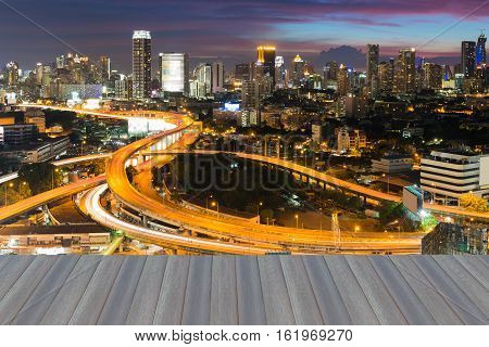 Open wooden floor, aerial view highway intersection with city downtown background night view