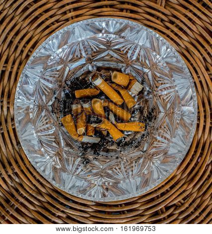 Overhead of burning cigarette in ashtray on wood table
