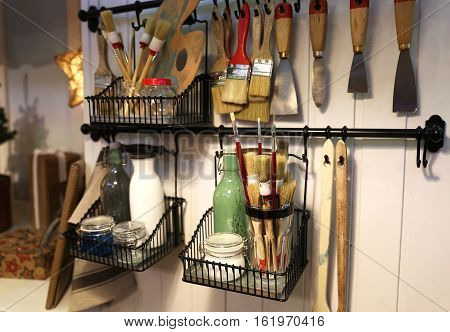 Some brushes with other needed stuff for repairing and making arts. They are located on the wall which is wooden