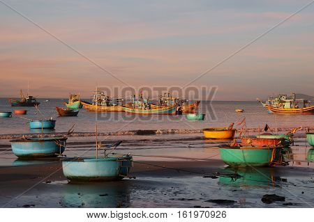 Vietnamese round fishing boat-baskets in the setting sun in Mui Ne Vietnam