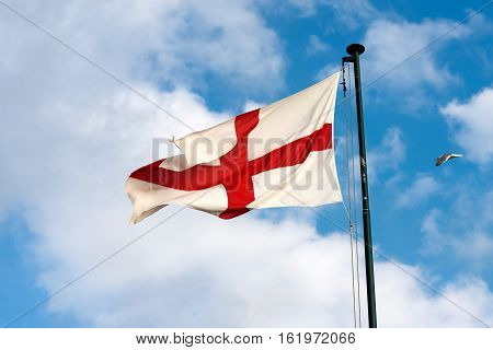 Flag of the city of Genova (Genoa - Italy) with the cross of St John the baptist on a blue sky with clouds