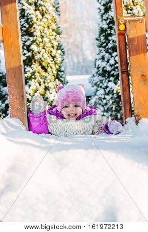 Little Babe Girl Playing On The Winter Playground.
