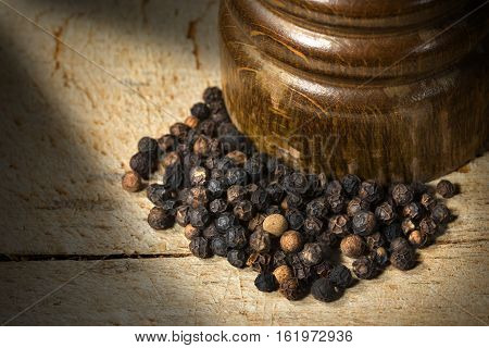 Macro photo of peppercorns and an old wooden pepper mill on wooden cutting board with dark shadows