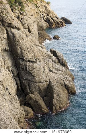 Rocky cliffs in the Mediterranean Sea in Portofino village. Genova Liguria Italy