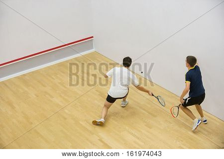 Squash players in action on squash court, back view