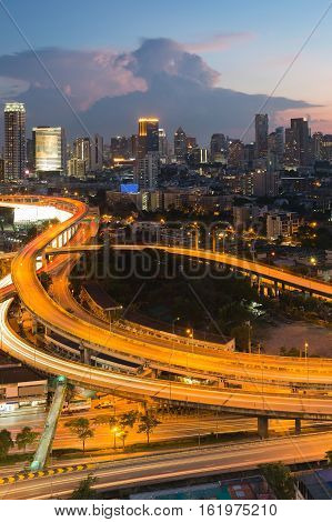 Long exposure highway interchanged with city downtown background at twilight