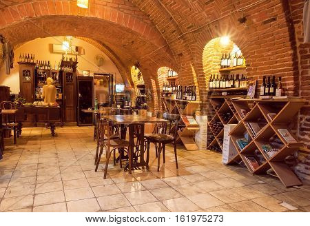 TBILISI, GEORGIA - SEP 26, 2016: Empty wine bar inside the old brick underground with restaurant furniture and wine bottles on September 26, 2016. Tbilisi has population of 1.5 million people