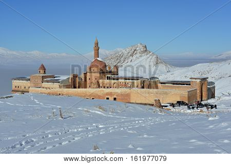 Ishak Pasha Palace among snowy mountains. Fog over valley and blue sky in background.