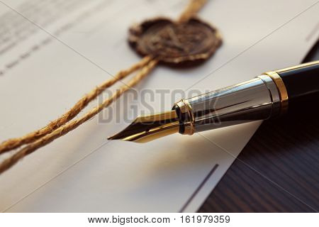 Fountain pen and old notarial wax seal on document, closeup