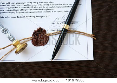 Old notarial wax stamp on document and pen, closeup
