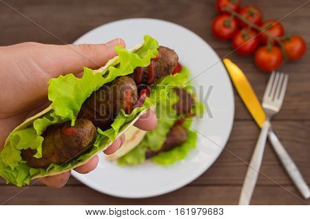 Tortilla with meat wrapped in bacon and herbs. Wooden background