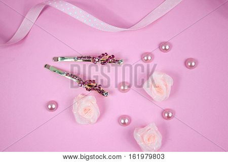 Golden hairpins with pink gemstone, pink pearls, pink textile roses and pink polka dot ribbon on pink background