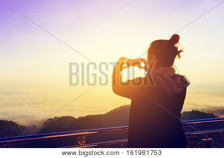 Silhouette of asian young woman taking photo with mountain and more foggy in winter.