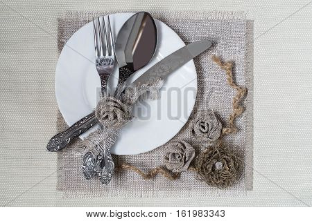 Burlap eco-friendly decor. DIY concept. Homemade napkin of burlap with handmade flowers for the table. Plate knife spoon fork on napkin of burlap. Vintage rustic style