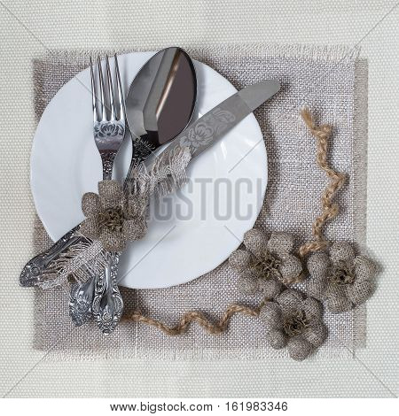 Burlap eco-friendly decor. DIY concept. Homemade napkin of burlap with handmade flowers for the table. Plate knife spoon fork on napkin of burlap. Vintage rustic style. Square image