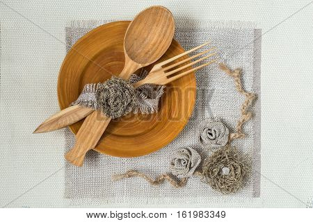 Burlap eco-friendly decor. DIY concept. Homemade napkin of burlap with handmade flowers for the table. Wooden plate spoon fork on napkin of burlap. Vintage rustic style