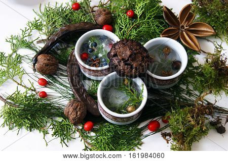 Three cups and chocolate cupcake on Christmas background