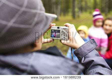 little offspring shooting his family in park outside, lifestyle people concept close up