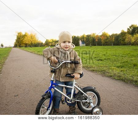 little cute real boy on bicycle emotional smiling close up outside in green amusement park real