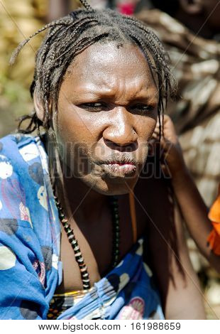 AFRICA, TANZANIA, MAY, 10, 2016 - Portrait typical woman with bead decoration and african pigtails of the Hadzabe tribe. Hadzabe tribe threatened by extinction in Tanzania, Africa