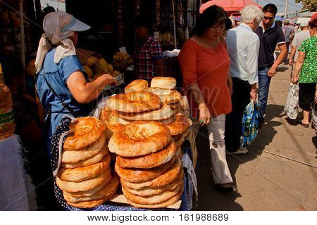 BISHKEK, KYRGYZSTAN - AUG 1, 2013: Vendors selling traditional Central Asian bread on the popular Osh market on August 1, 2013. In Kyrgyzstan 34 perc. are under age of 15 and 6.2 perc. are over 65.