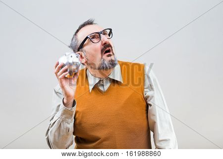Nerdy man is worried because he is having problem with saving money.