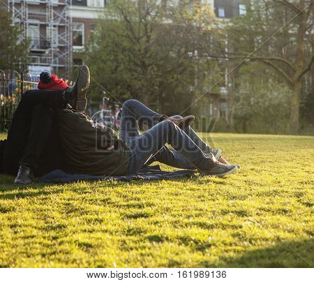 two young guys hipsters chilling on green grass outside in park at sundown, relaxing people lifestyle concept, couple from back