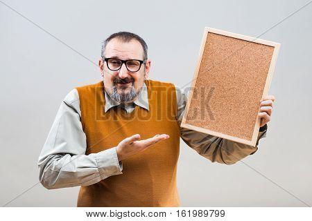 Nerdy businessman is holding empty cork board .