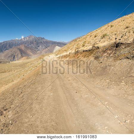 Dirt road through arid mountain wastelands. Muktinath region in Nepal.