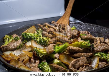 beef broccoli and onion stirfry steaming in a pan