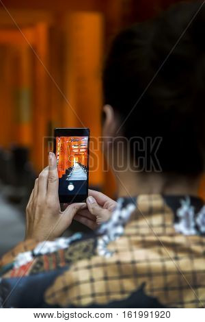 KYOTO, JAPAN - OCTOBER 8, 2016: Unidentified woman at walkway in Fushimi Inari shrine in Kyoto Japan. This popular shrine have 32000 sub-shrines throughout Japan
