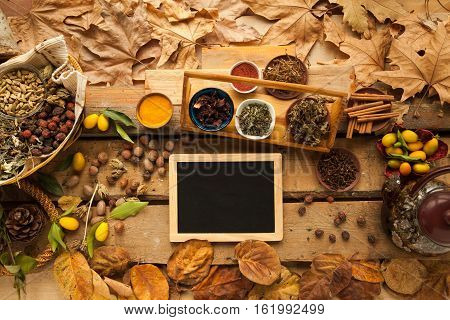 Ingredient for preparing healthy tea with spices and carnation, free space on blackboard, you can place your recipe.