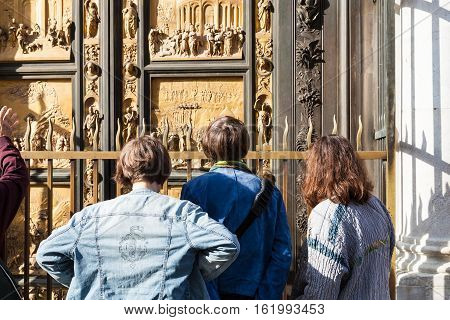 Tourists Look On East Doors Of Baptistery