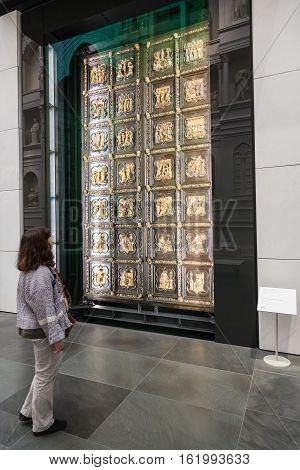 Tourist Near Original Doors Of Florence Cathedral