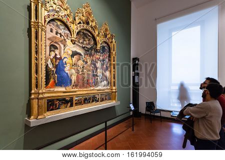 Visitors View Painting In Room Of Uffizi Gallery