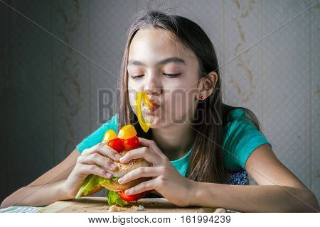 11 Year Old Girl Sitting And Eating A Hamburger With Eyes Of Cherry Tomatoes And Capsicum.