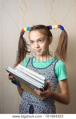 11 Year Old Girl With Funny Tails Is With A Pile Of Books. Concept Of School Education