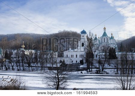 Siversky Donets River winter. On the opposite bank the Cathedral of the Assumption and the Holy Church of the Intercession. Sviatohirsk Lavra Ukraine