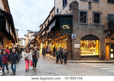 Tourists Walk On Ponte Vecchio In Florence City