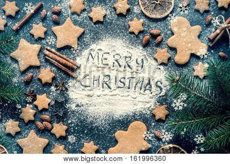 Merry Christmas greeting written on flour on blackboard. Frame with gingerbread stars cookies, gingerbread man cookies, stars, spices, cinnamon sticks, fir tree and Christmas decorations. Top view