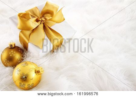 Gold ribbon gifts with christmas ornaments on fur