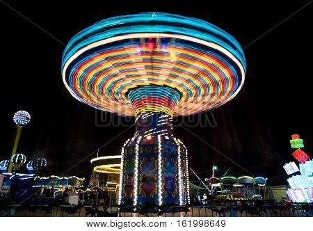 Merry go round Carousel spinning fast creating wonderful light trails at an amusement park.