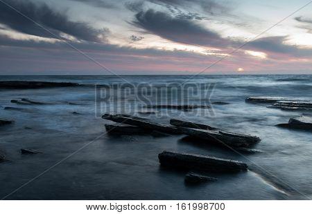 Sunset on a rocky beach. Long exposure